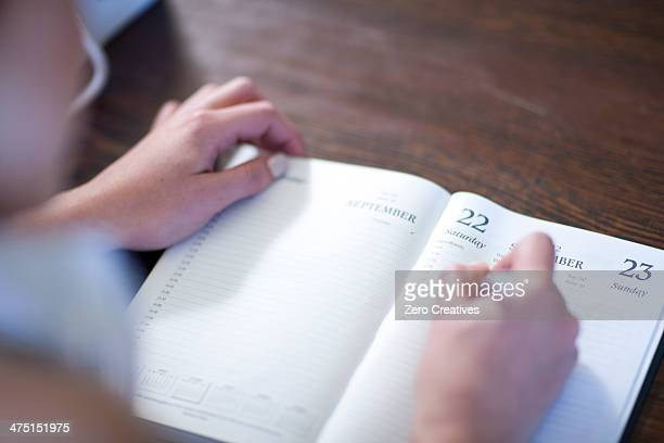 close up of female writing in diary - schedule stock photos and pictures
