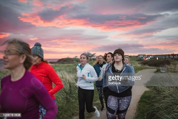 close up van vrouwen lopen langs een pad op het strand - noordoost engeland stockfoto's en -beelden
