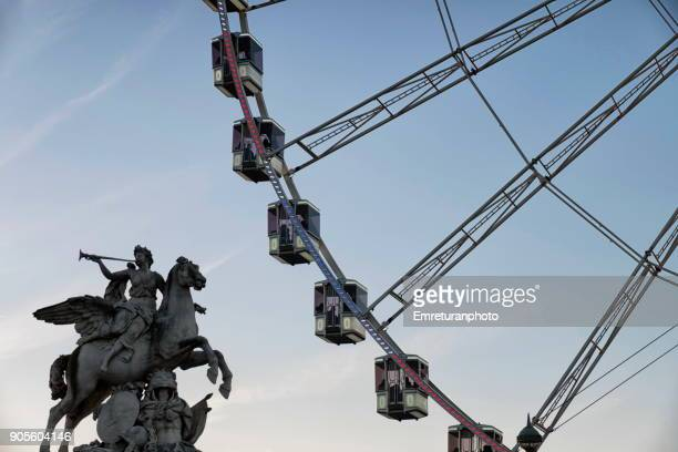 Close up of ferris wheel and with silhouette of a statue nearby ar sunset,Paris.