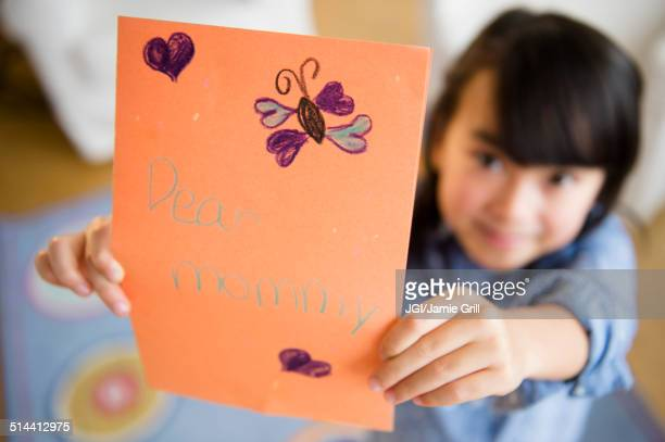 Close up of Filipino girl holding card for mother