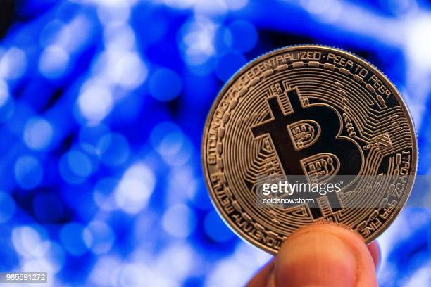 close up of fingers holding golden bitcoin cryptocurrency with fluctuating multi colored graph infographic background - bitcoin stock pictures, royalty-free photos & images