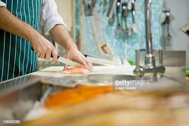 Primer plano de fishmonger corte pescado