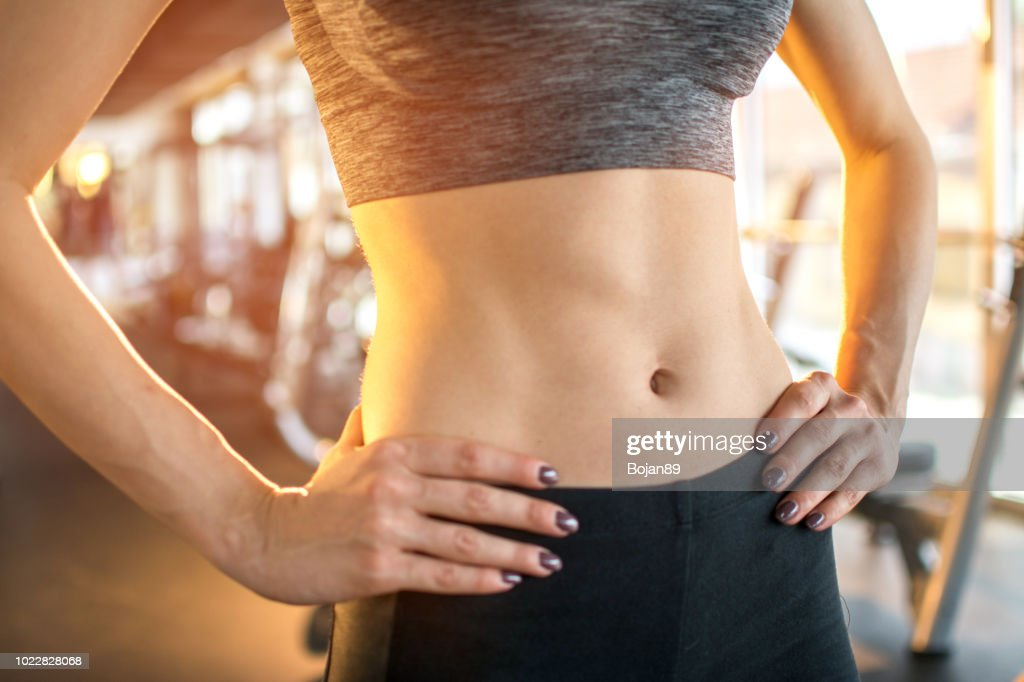Close up of fit woman's torso with her hands on hips at gym : Stock Photo
