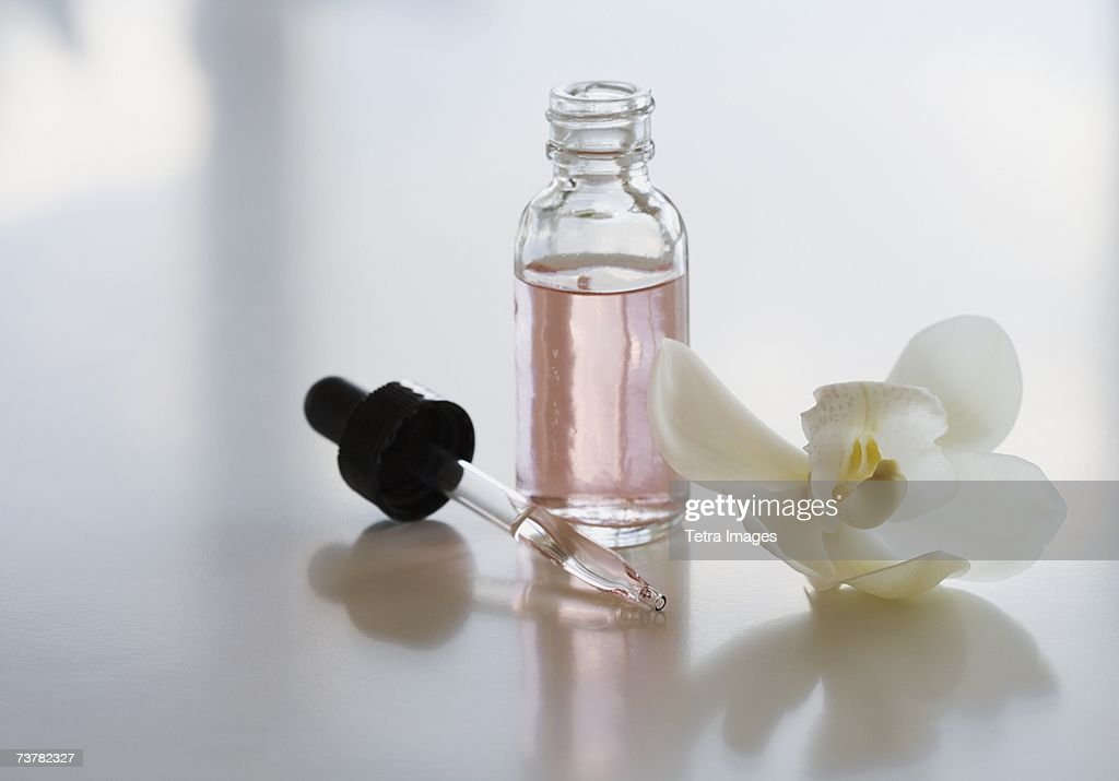 Close up of flower and bottle of oil : Stock Photo