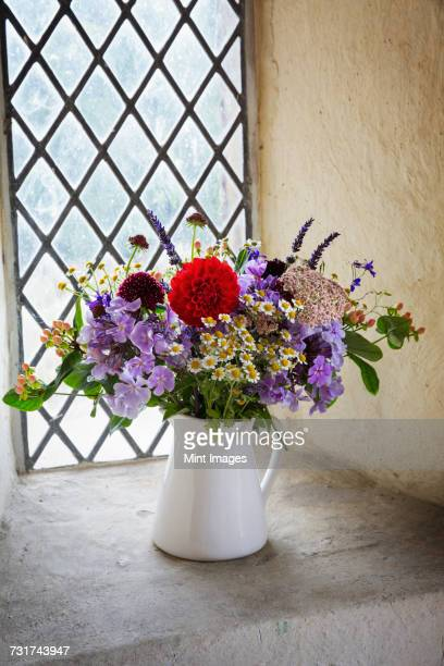 Close up of flower bouquet in a white jug on a windowsill.