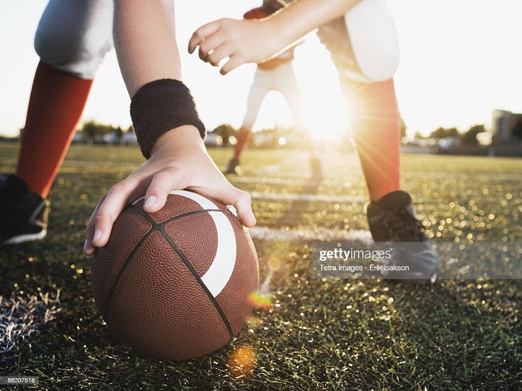 Close up of football center preparing to snap football : Foto de stock
