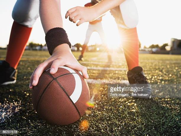 close up of football center preparing to snap football - quarterback stock photos and pictures