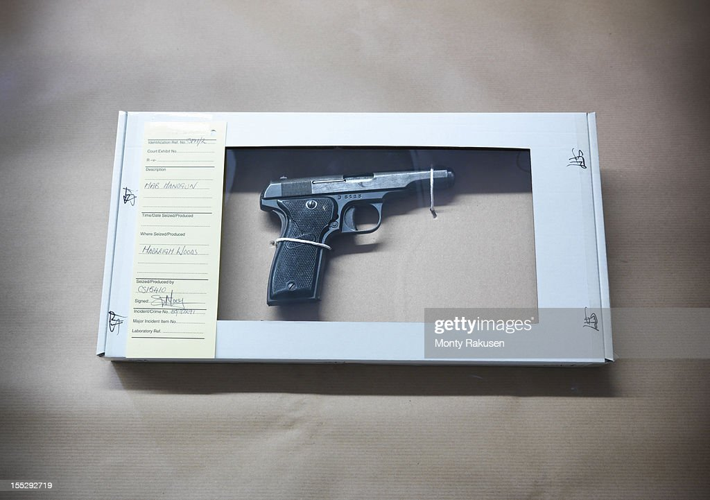 Close up of forensic science evidence box containing gun from crime scene : Stock Photo