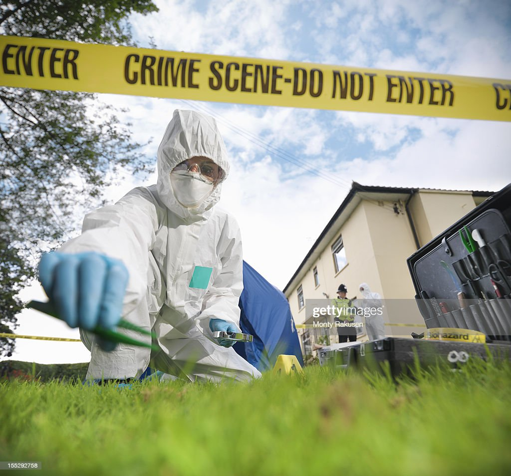 Close up of forensic scientist taking sample at crime scene, surface level view : Stock Photo