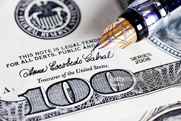 Close up of fountain pen nib on $100 bill