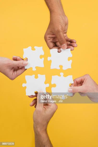 Close up of four hands holding puzzle pieces