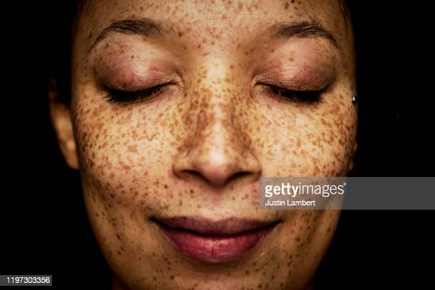 close up of freckles on mixed race woman with her eyes closed - serious stock pictures, royalty-free photos & images