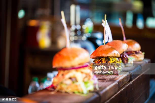 close up of fresh flame grilled burgers displayed in a row at food market - restaurant stock photos and pictures