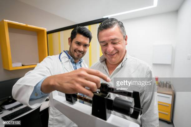 close up of friendly doctor and patient talking while doctor is adjusting the scale to measure patients weight - mass unit of measurement stock pictures, royalty-free photos & images