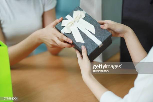 close up of friends giving gift box - 手渡す ストックフォトと画像