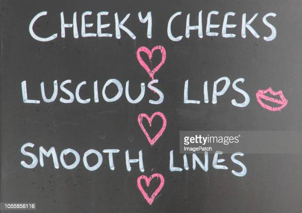 close up of funny sexy street side advertising chalkboard sign for a beauty parlor. - sexy drawing stock pictures, royalty-free photos & images