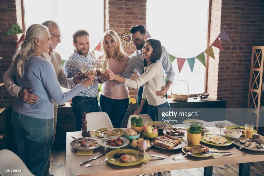 Close up of gathered relatives in decorated house dinner table with glasses golden beverage in hands family best friends wishing all great big large company : Stock Photo