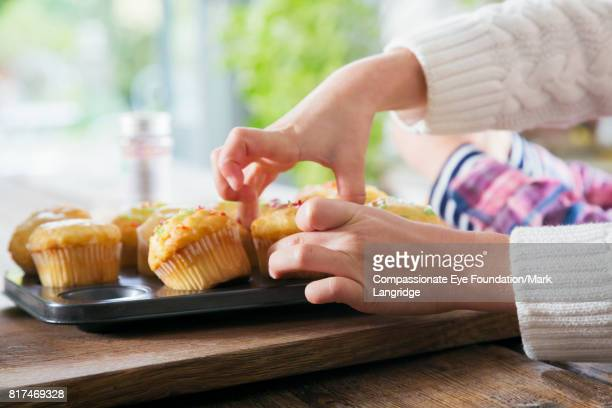 Close up of girl decorating cup cakes in kitchen