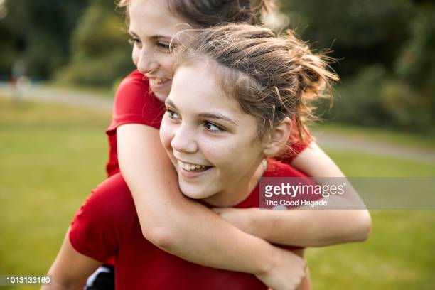 close up of girl giving friend a piggyback ride - giving a girl head stock photos and pictures
