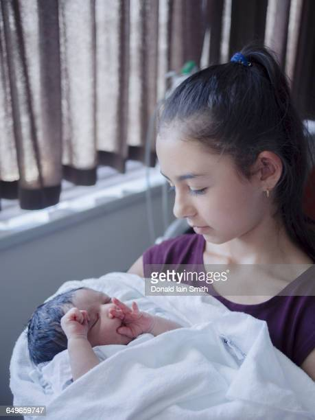 Close up of girl holding newborn baby brother