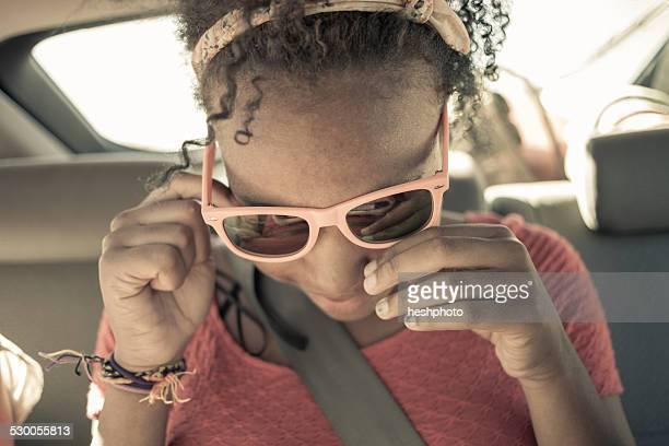close up of girl peering though sunglasses on car back seat - heshphoto foto e immagini stock