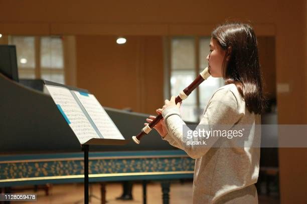 close up of girl playing recorder in music room. - recorder musical instrument stock photos and pictures
