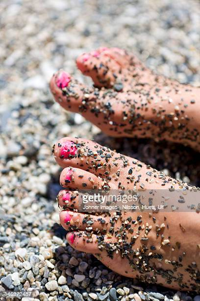 Close up of girls feet with pink nail polish covered with pebble stones