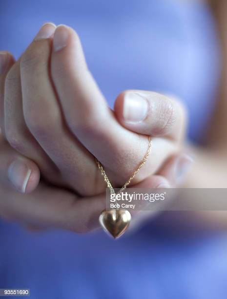 Close up of girl's hand holding heart necklace.