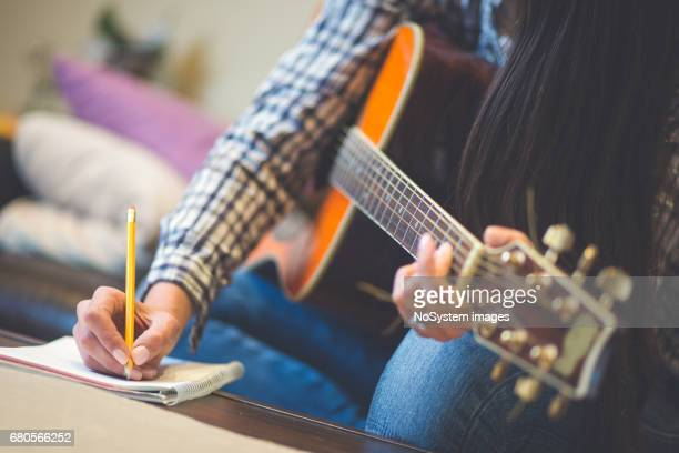 Close up of girls hand writing down music, playing a guitar. Shallow DOF, focus on hand and pencil.