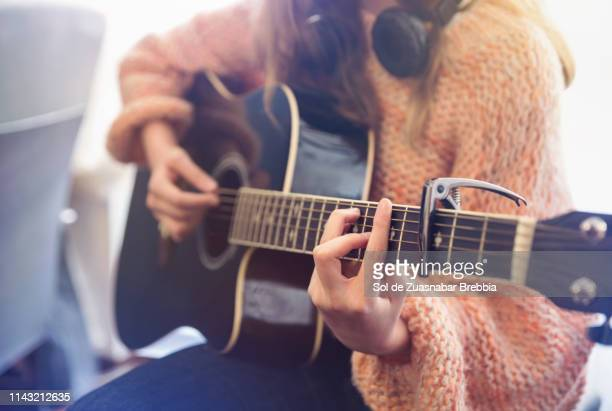 close up of girl's hands playing the guitar - guitar stock pictures, royalty-free photos & images