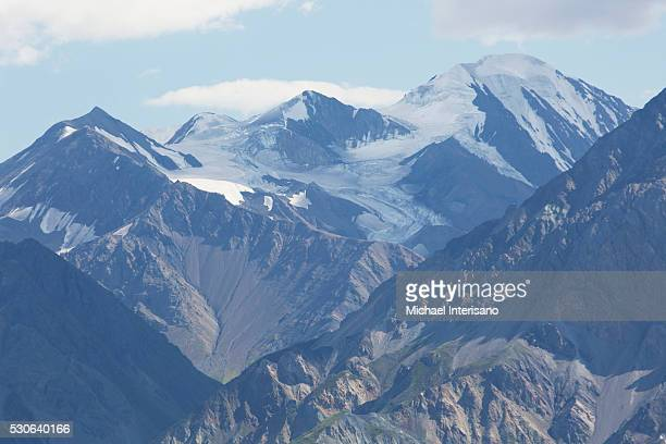 Close up of glacier mountains with blue sky and clouds; Yukon, Canada