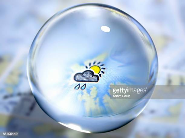 close up of glass ball with rain cloud and sun in center - weather stock pictures, royalty-free photos & images