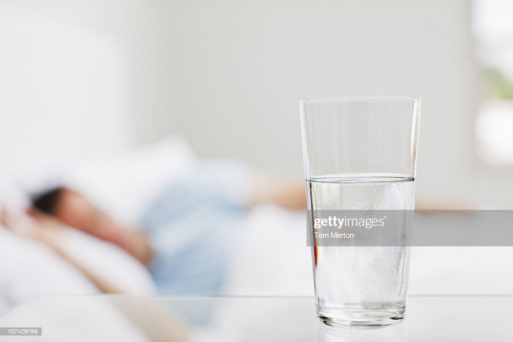 Close up of glass of water with sick man in background : Stock Photo