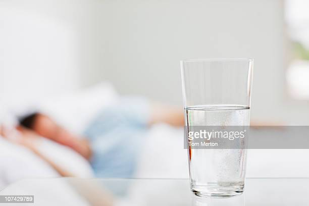 close up of glass of water with sick man in background - thirsty stock pictures, royalty-free photos & images