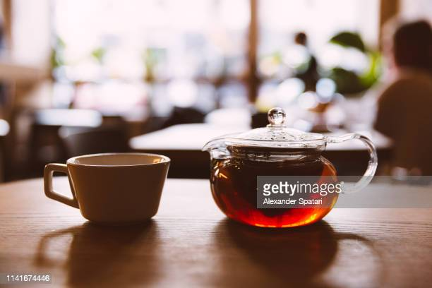 close up of glass teapot and tea cup on the table in a cafe - tea room stock pictures, royalty-free photos & images