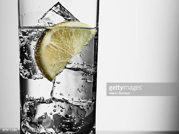 Nahaufnahme von einem Glas mit Wasser, Eiswürfel und Zitrone