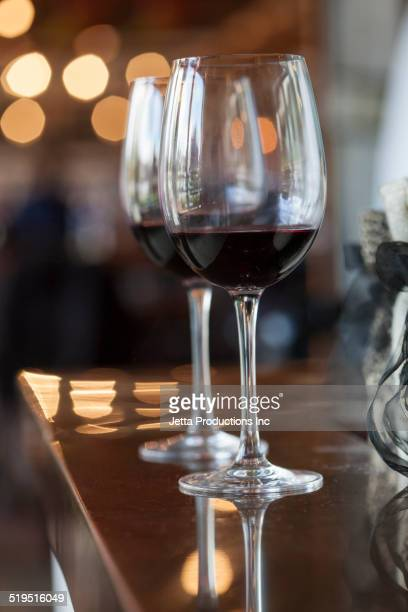 Close up of glasses of red wine on bar