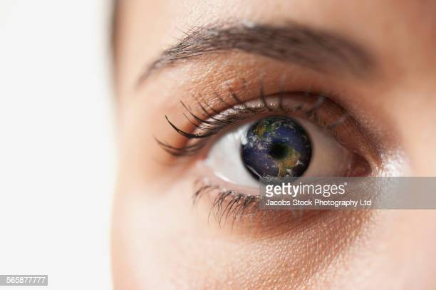 Close up of globe in mixed race womans eye
