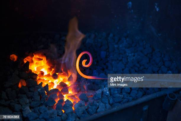 Close up of glowing metal rod with a scrolled end, held over hot coals in a blacksmiths workshop.