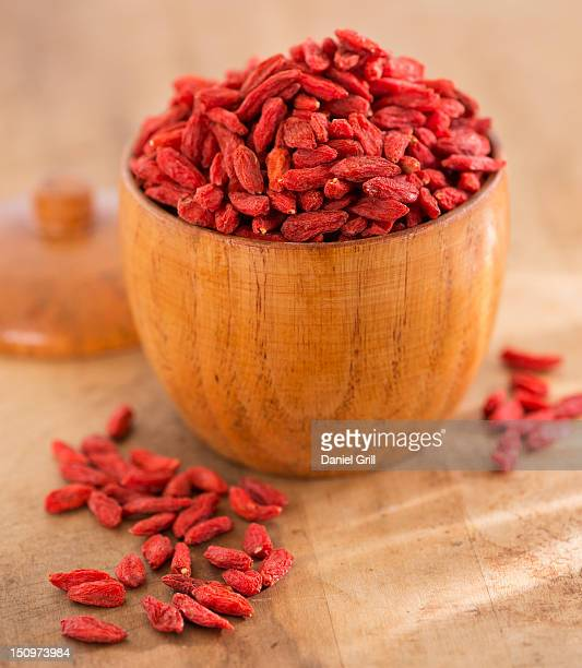 Close up of goji berries in wooden bowl, studio shot