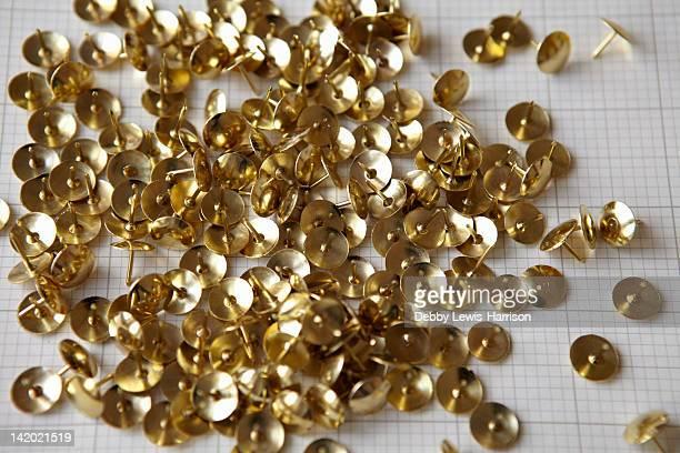 Close up of gold thumbtacks