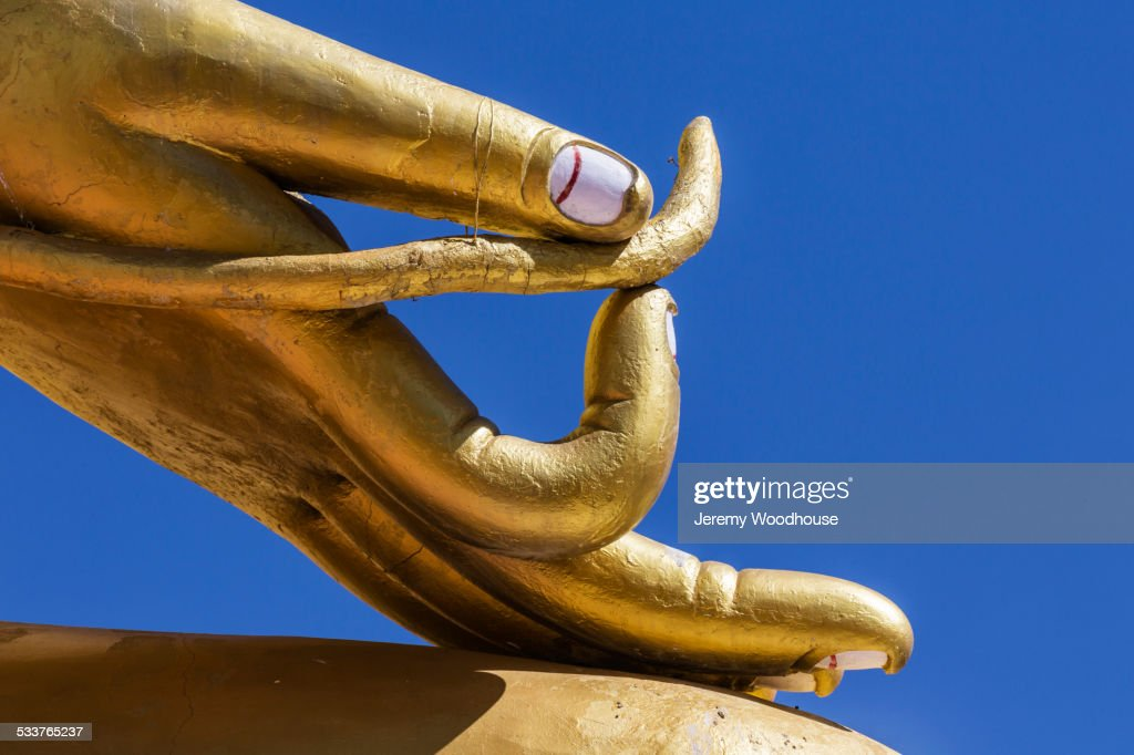 Close up of golden hand statue against blue sky : Foto stock