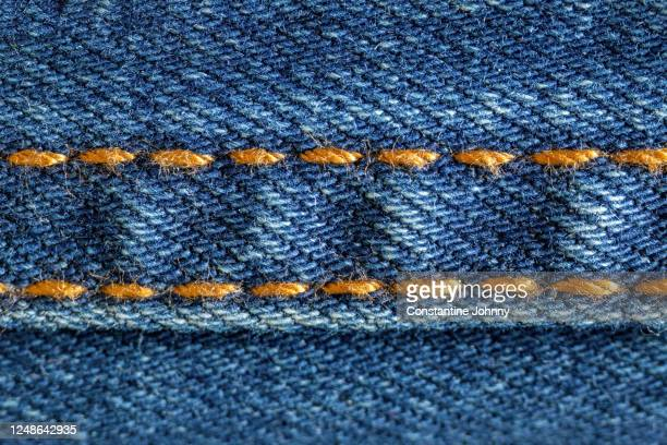 close up of golden stitches on blue denim jeans - sewing stock pictures, royalty-free photos & images