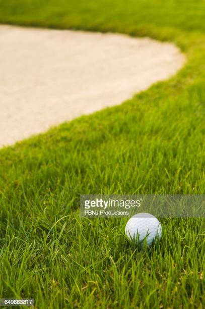close up of golf ball near sand trap on golf course - foco diferencial imagens e fotografias de stock