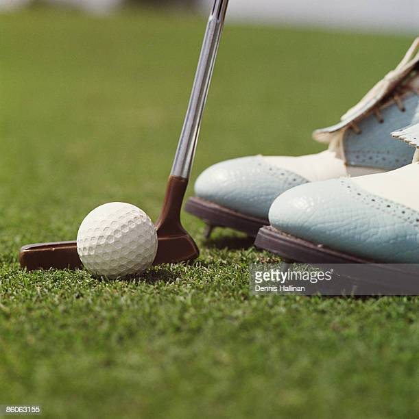 Close up of golf ball , putter and shoes on grass