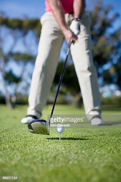Close up of golf club about to hit golf ball