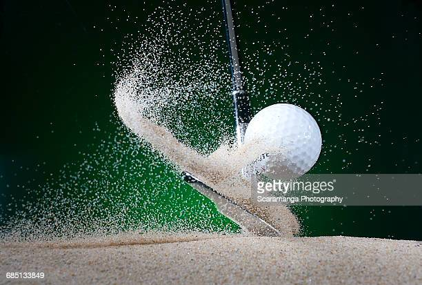Close up of golf club hitting ball in bunker