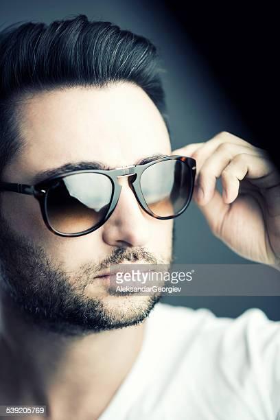 Gros plan de beau homme avec barbe portant des lunettes de soleil