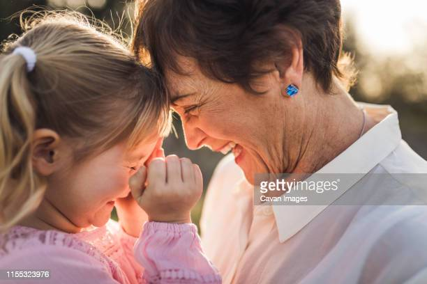 close up of grandmother and granddaughter looking at each other and la - grandmother stock pictures, royalty-free photos & images