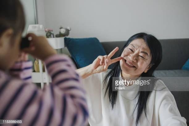 close- up of grandmother face while photo shoot at home - asian granny pics stock photos and pictures